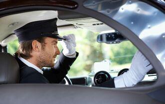 Elegant chauffeur in luxurious car